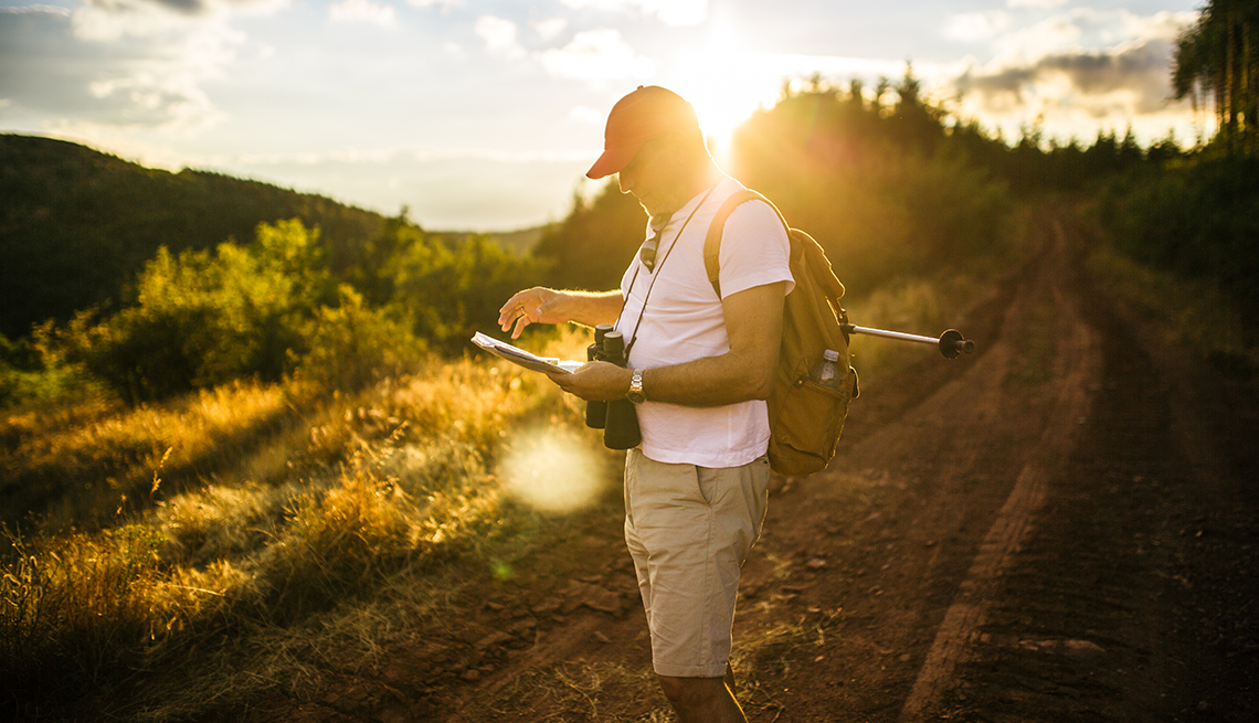 man standing on a trail with a notebook and binoculars