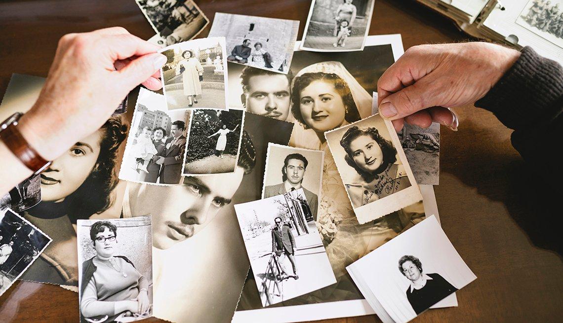 Dos manos sostienen fotos antiguas de retratos de personas
