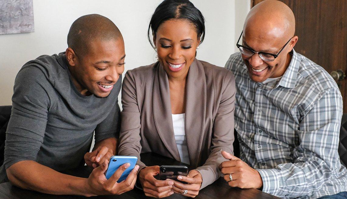 Una mujer y dos hombre observan fotos en sla pantalla de sus teléfonos