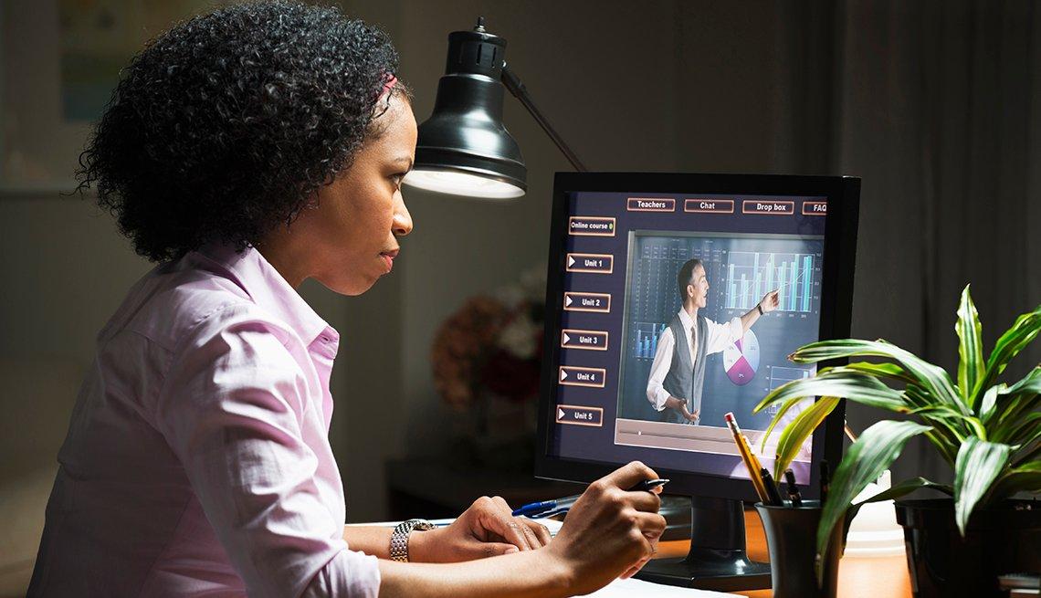 Mujer sentada frente a una computadora atiende un curso en línea