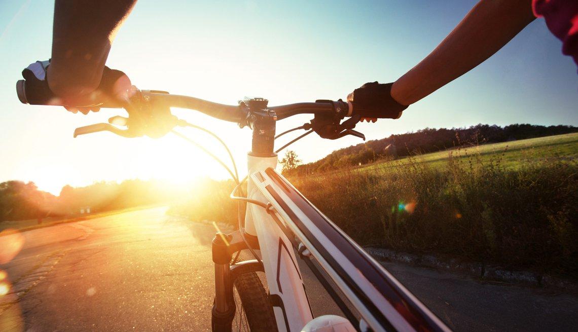 Persona sostiene el manubrio de una bicicleta