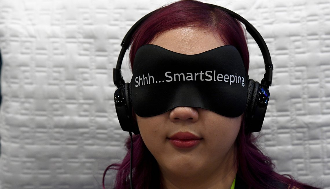 Woman wears eye mask and headphones