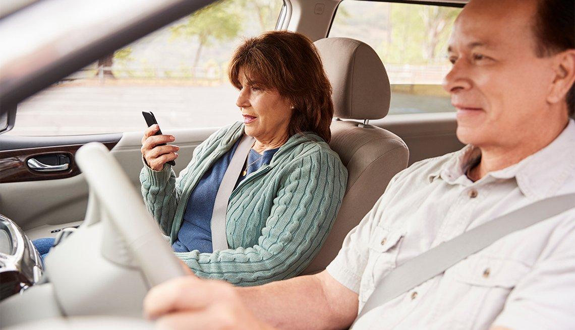 Mujer pasajera observa el GPS en el teléfono durante un viaje en automóvil