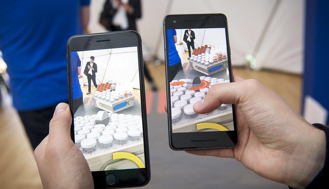 Persona sostiene en sus manos un teléfono inteligente Android y un iPhone de Apple con sistema operativo IOS
