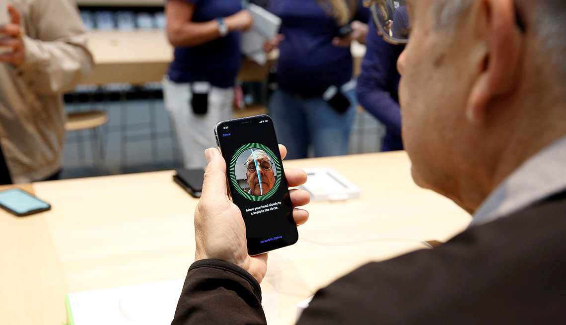 Mature man holds an iPhone X and looks at a mirror image of himself inside of an Apple Store.