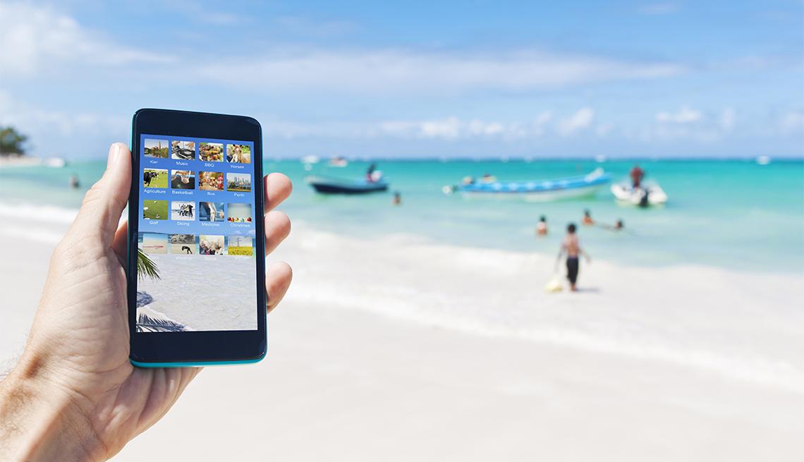 Mano de una persona sostiene un teléfono inteligente y al fondo se ve una playa de Punta Cana, República Dominicana