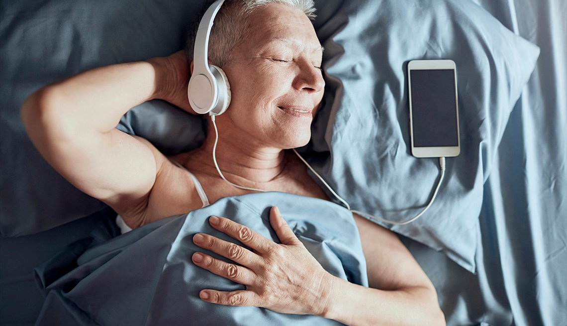 Una señora mayor escuchando música mientras está acostado en la cama