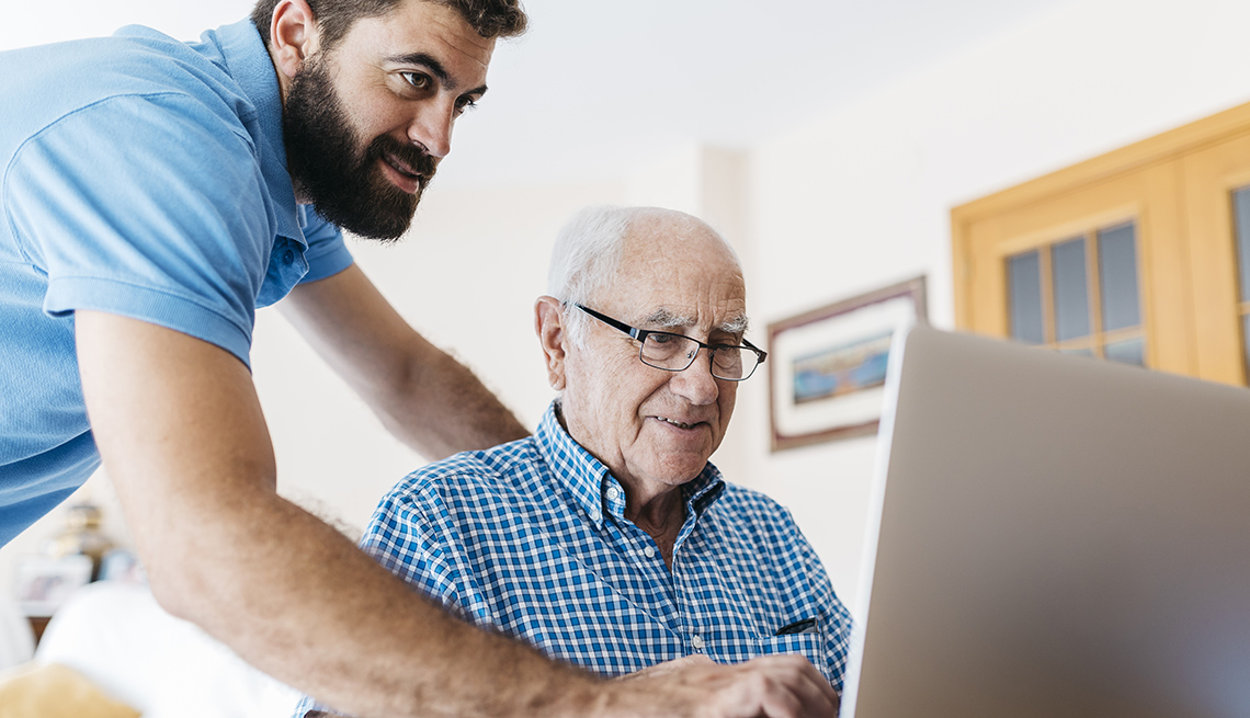 Grandson teaching his grandfather to use the computer and surf the internet.