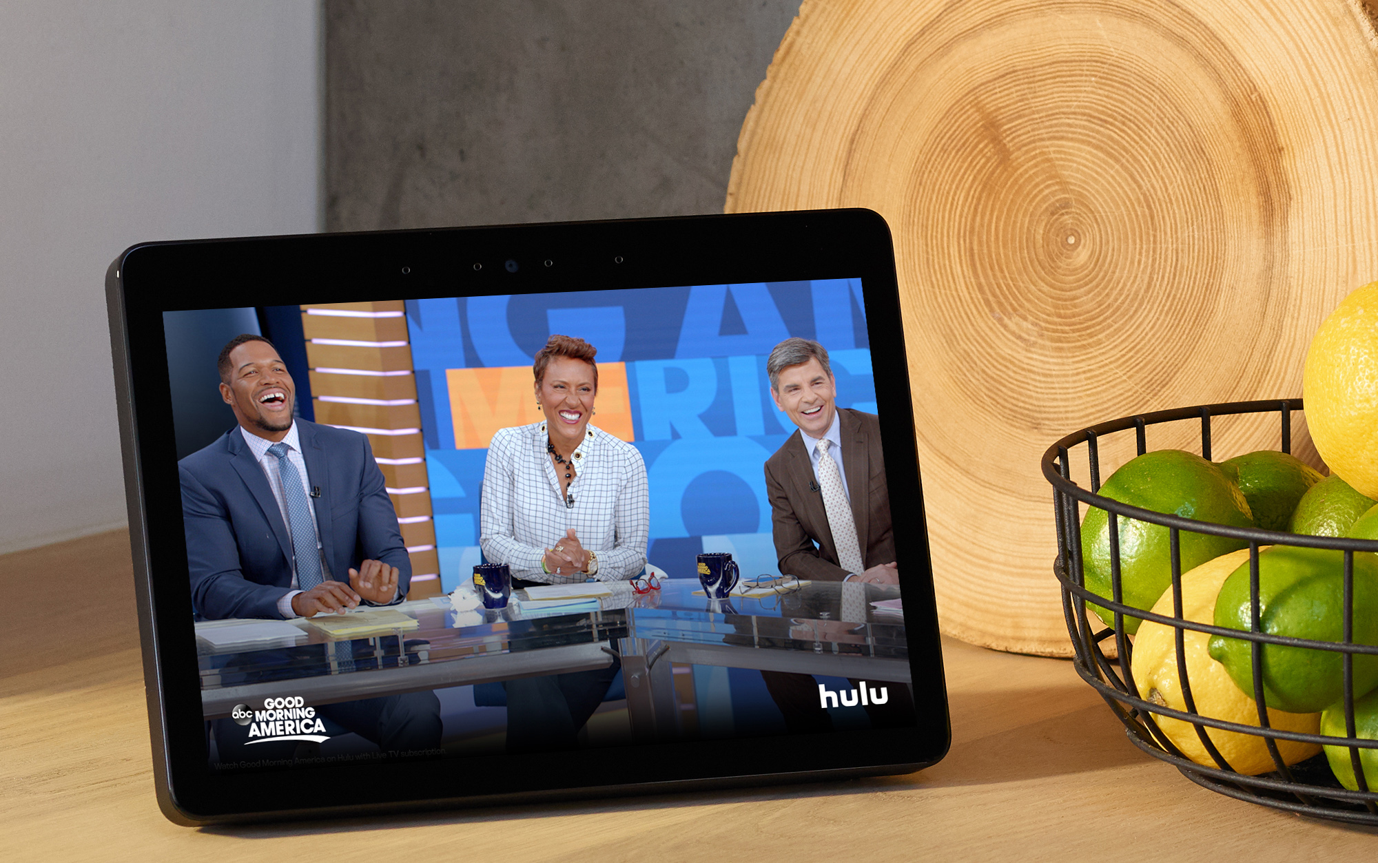 item 4 of Gallery image - Amazon Echo show on a wooden table next to a bowl of fruit