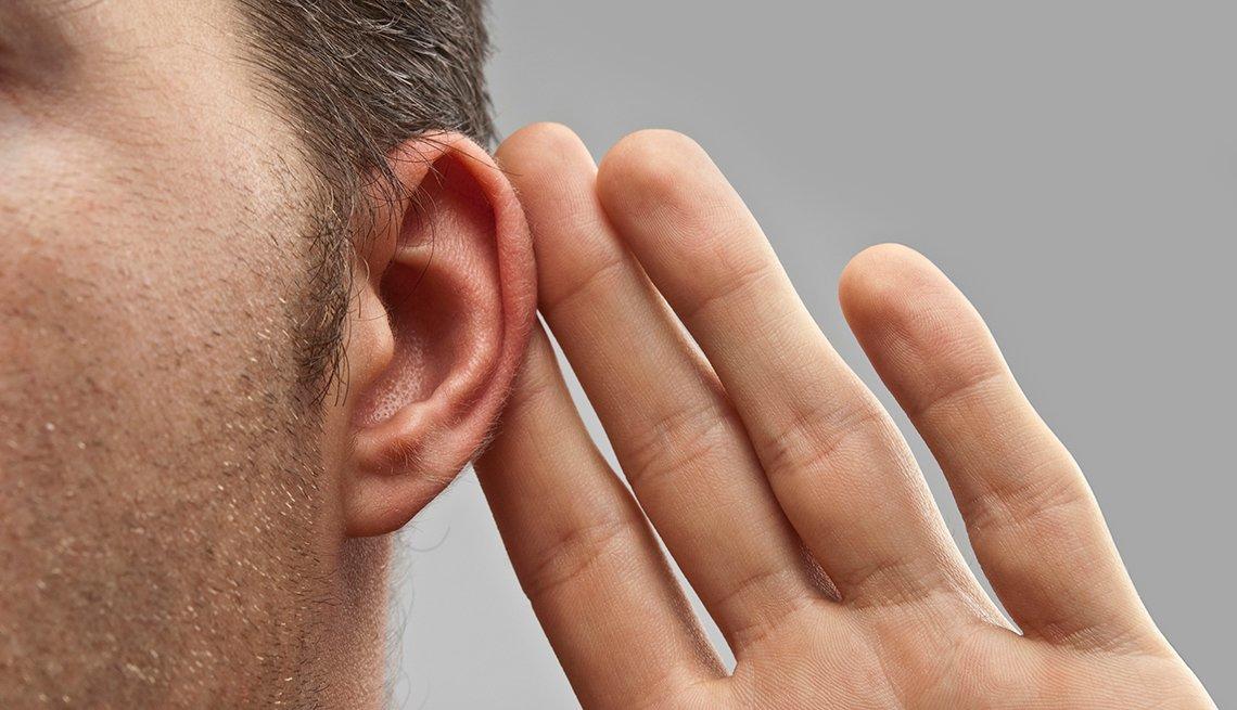 Vista cercana de un hombre que lleva sus dedos a la oreja haciendo un gesto de escuchar