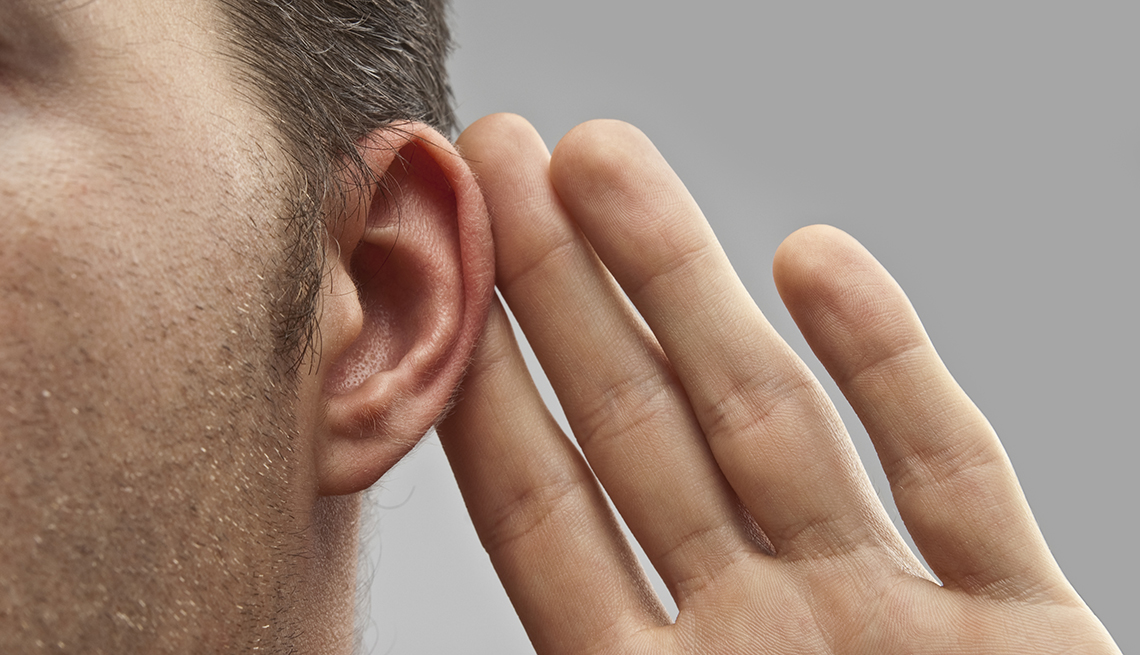close up view of a man holding his fingers up to his ear in the universal gesture of listening