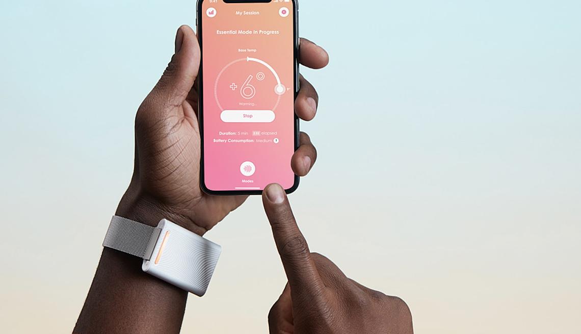 Mano lleva puesta una pulsera blanca y se ve una aplicación abierta en un teléfono móvil