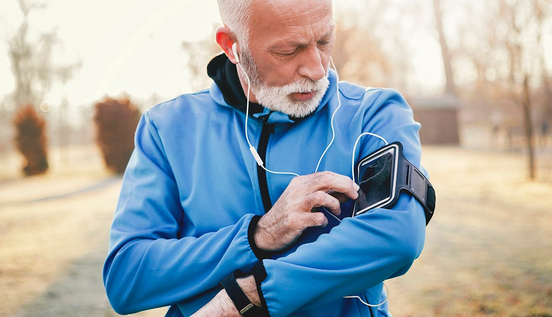 Older male checks his smartphone for missed call while jogging.