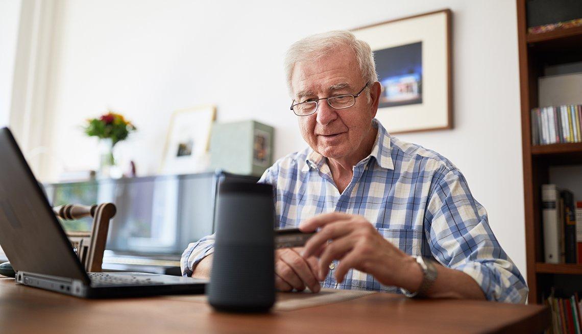 Hombre mayor sentado en el escritorio de la oficina en casa con una tarjeta de crédito y hablando con un altavoz inteligente