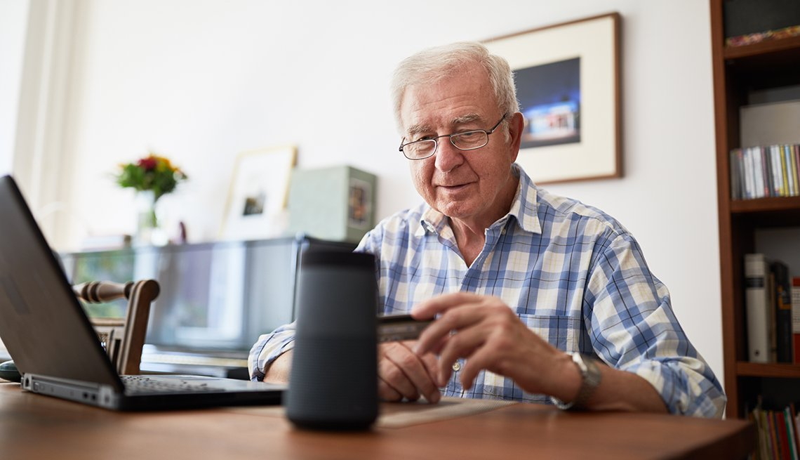 older man sitting at desk in home office holding a credit card and talking to smart speaker while making an online purchase