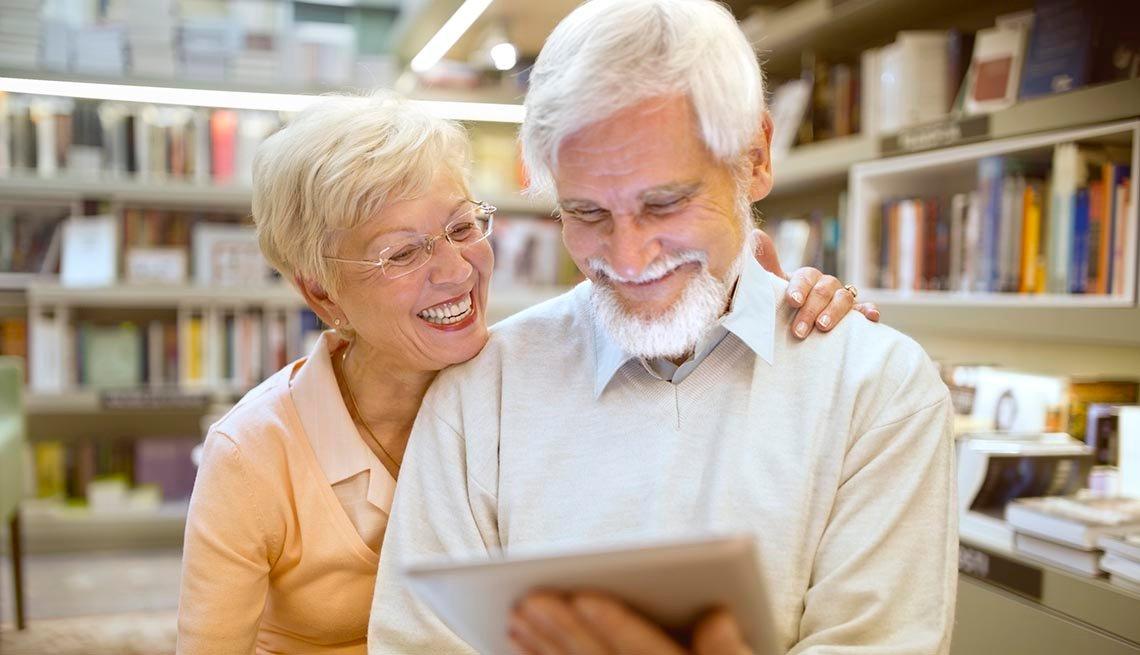 Un hombre y una mujer leen en la biblioteca con la ayuda de una tableta digital