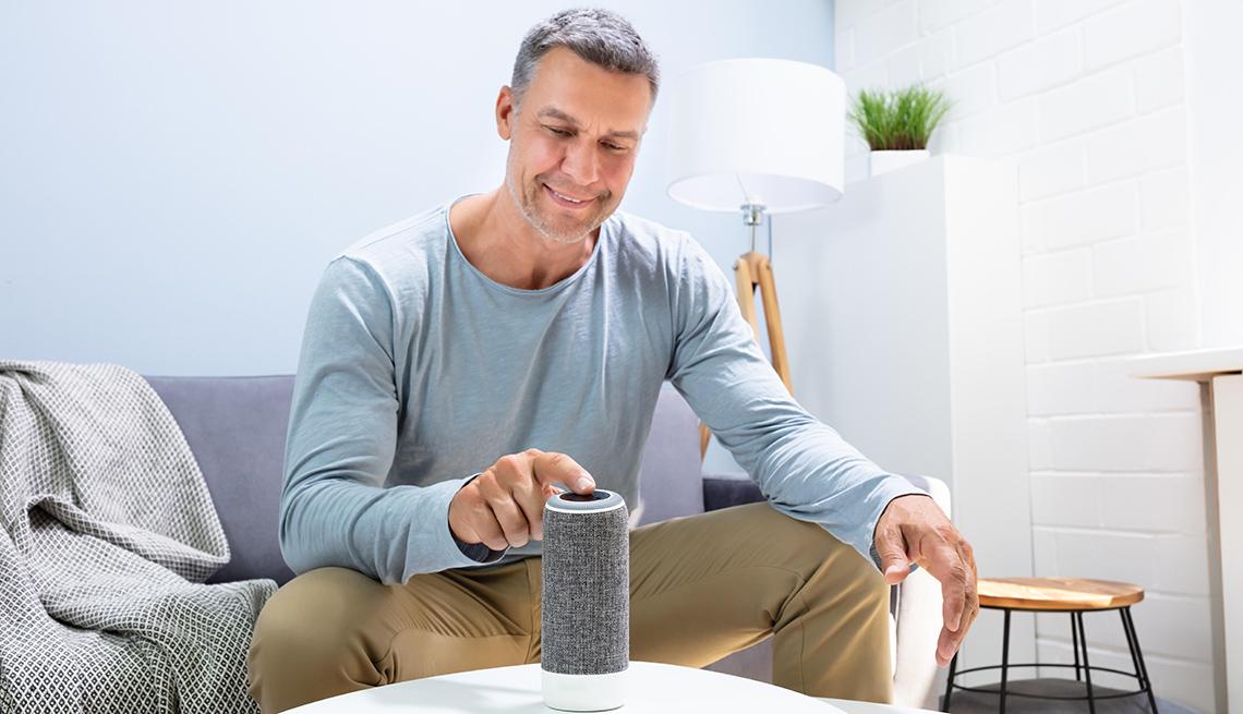 Hombre presiona un botón del altavoz inteligente en casa
