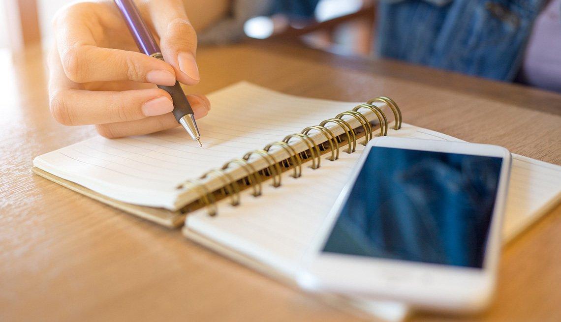 Persona escribe en un cuaderno de notas, también se puede ver un teléfono inteligente