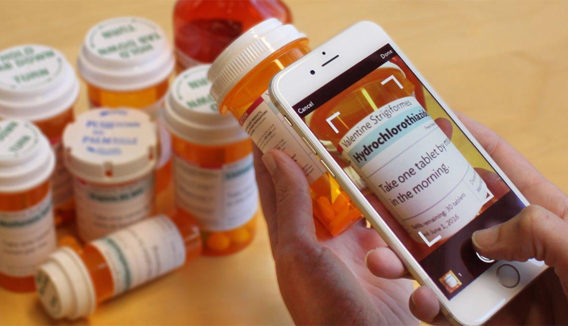 Una persona sostiene un teléfono inteligente en una mano y toma una foto de un frasco de pastillas