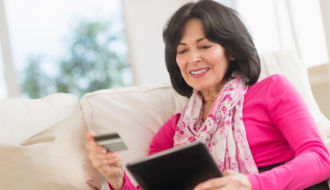 Mujer compra en línea con su tarjeta de crédito en la mano