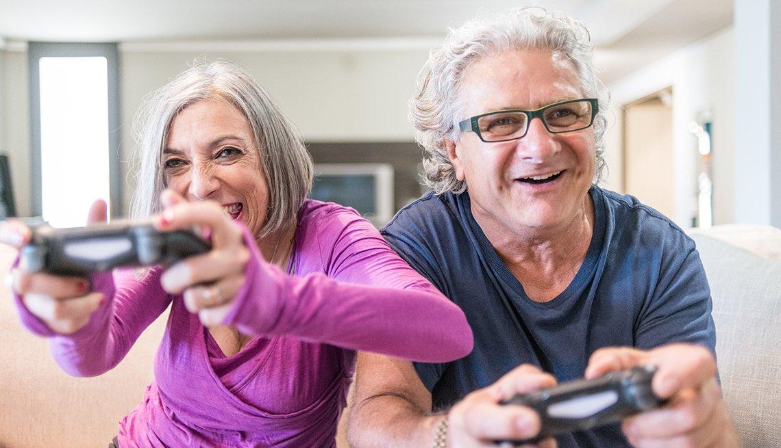 Pareja de abuelos sentados felices en el sofá con controles de videojuegos en sus manos