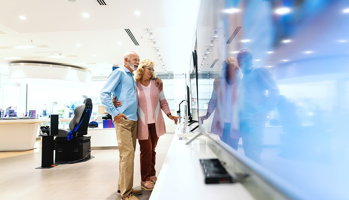 Happy old married couple hugging and looking for new plasma tv to buy. Tech store interior.