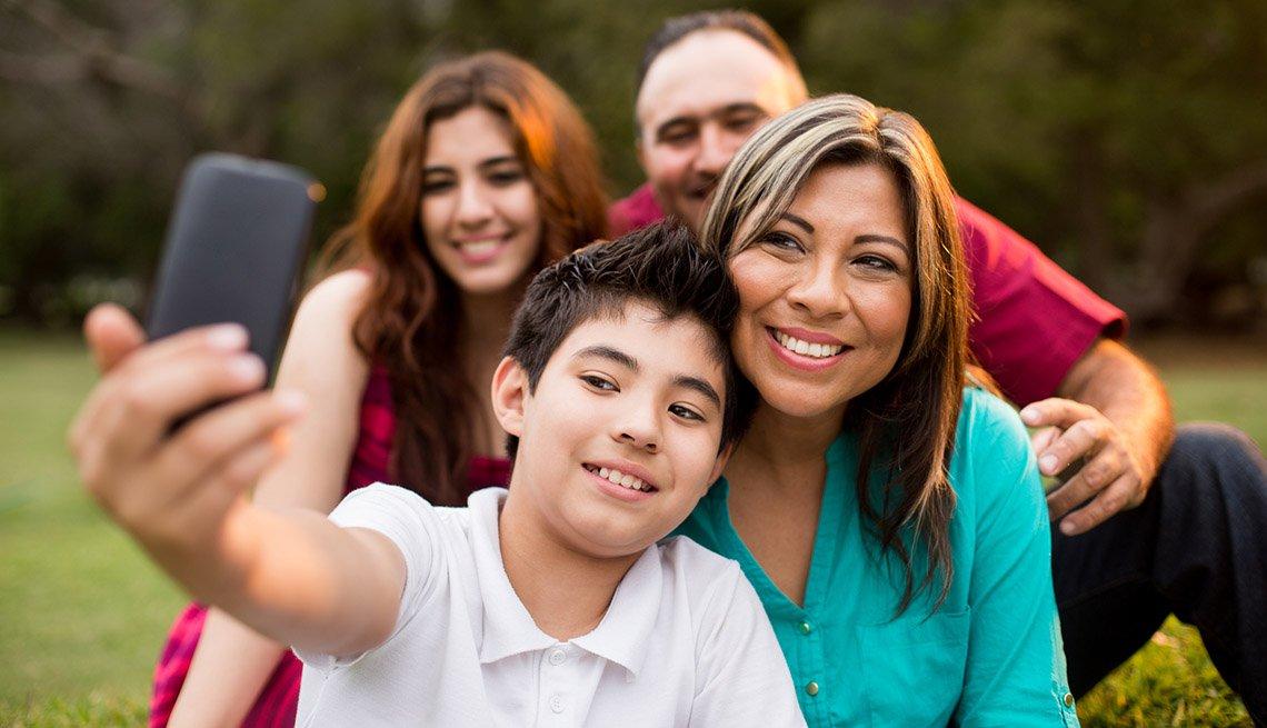 Un hijo adolescente, junto a su familia, toma una foto selfie con un teléfono móvil