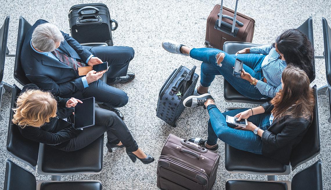 Viajeros en el aeropuerto manipulan sus dispositivos inteligentes