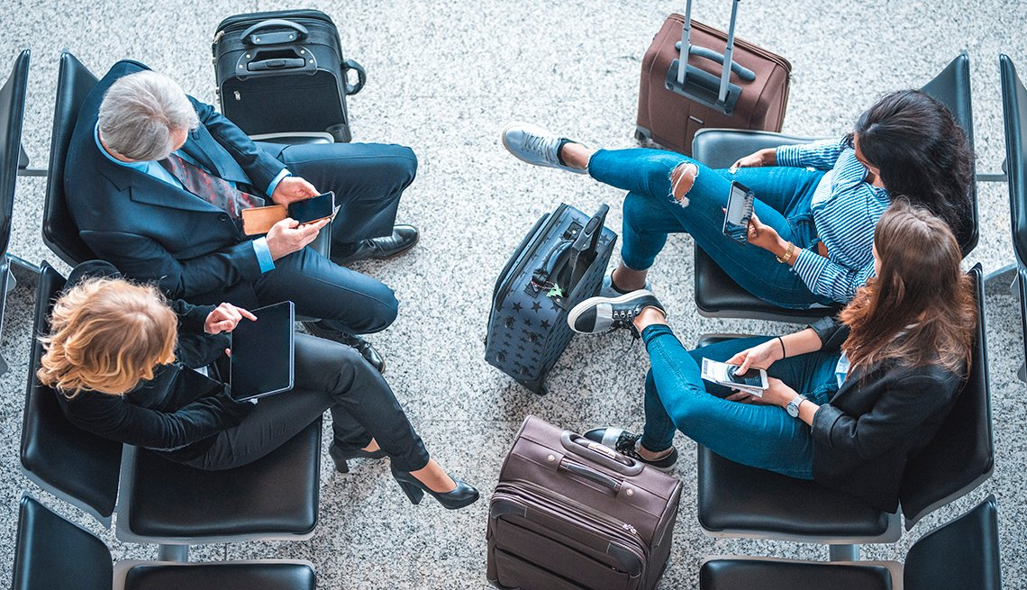Travelers at airport on smart devices