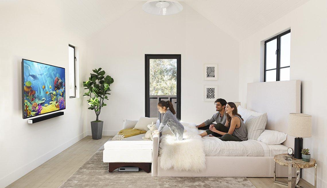 Una pareja en una habitación mira un programa de televisión infantil con su hija