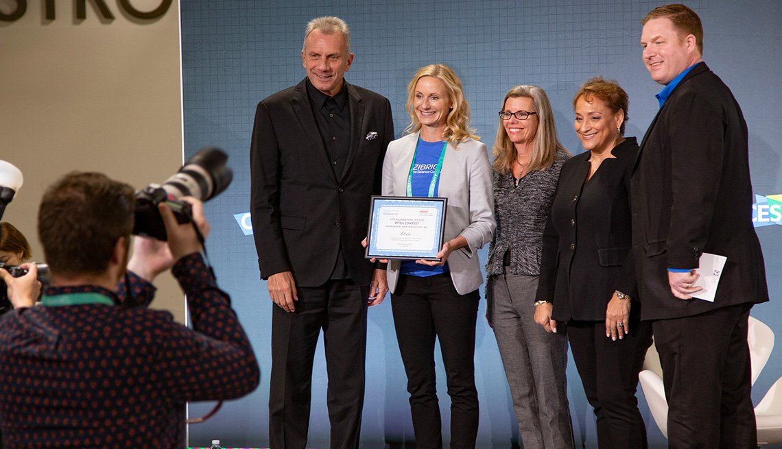 The winner of AARP's Innovation Pitch Contest,  CEO Jo Ann Jenkins and Joe Montana all pose on stage for a photograph