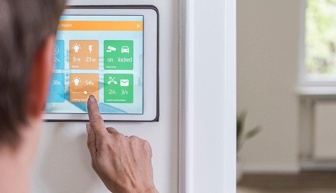 Mujer ajusta las luces de techo en un dispositivo doméstico inteligente