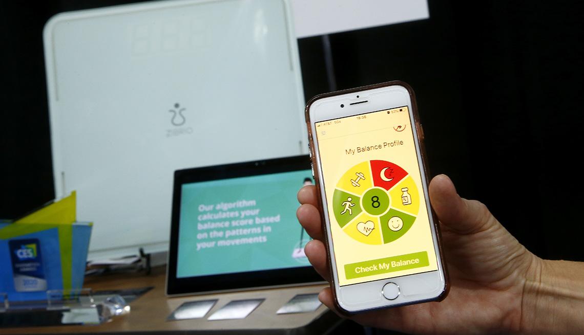 Persona sostiene un teléfono en la mano mientras muestra la aplicación Balance Coach