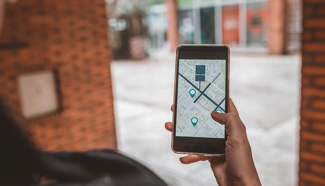 Persona usa el mapa en una aplicación del teléfono para navegar y encontrar su automóvil estacionado
