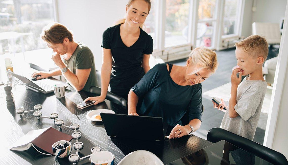 Familia usando dispositivos tecnológicos en el comedor