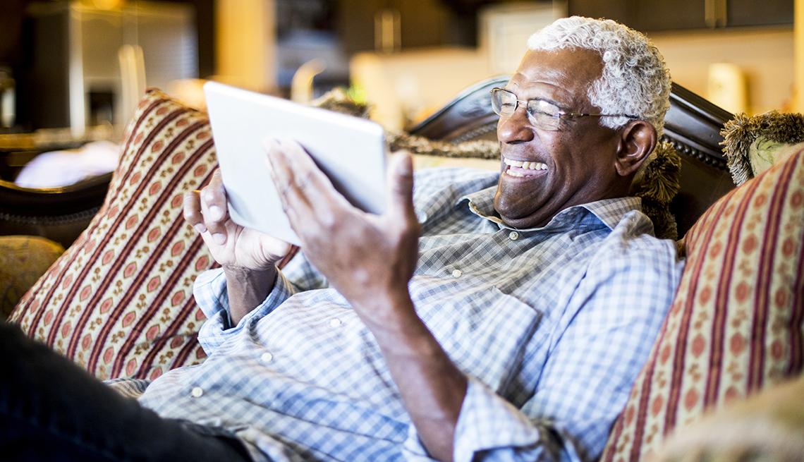 Un hombre sostiene una tableta en la mano mientras está en el sofá