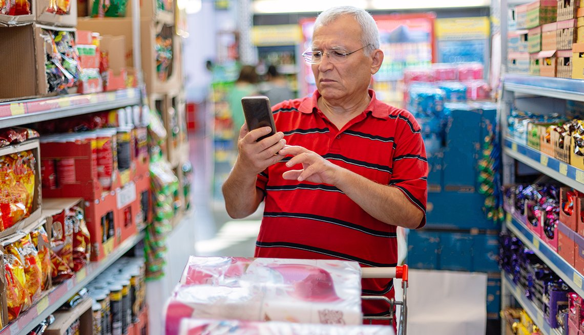 Seniorman checking shopping list on his smartphone