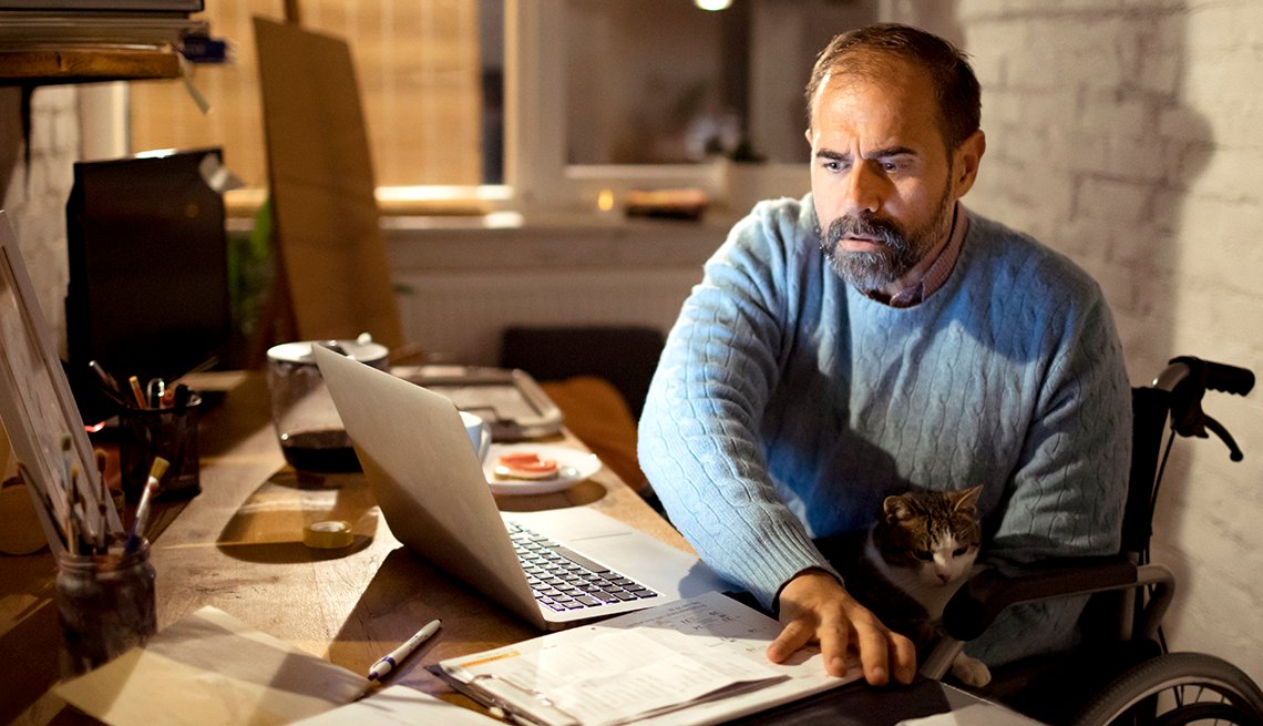 man in wheelchair sitting at his desk at home working with his cat on his lap