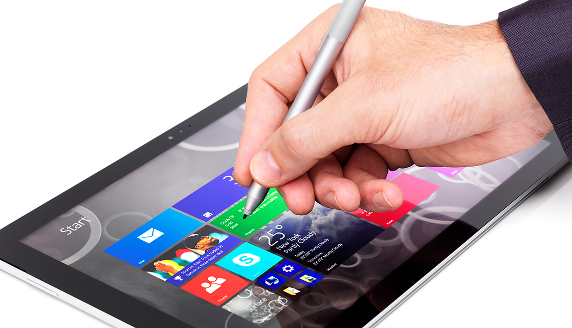 Person using Microsoft Surface Pro 3 tablet computer closeup of a hand with a stylus pen isolated on white background
