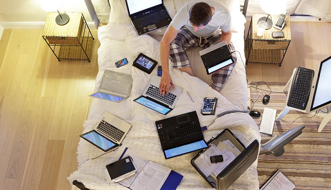 Hombre sentado en la cama rodeado de computadoras