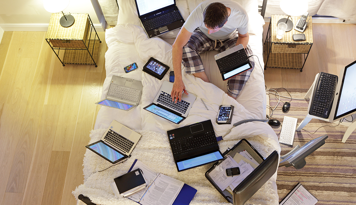 Man sat on bed surrounded by computers