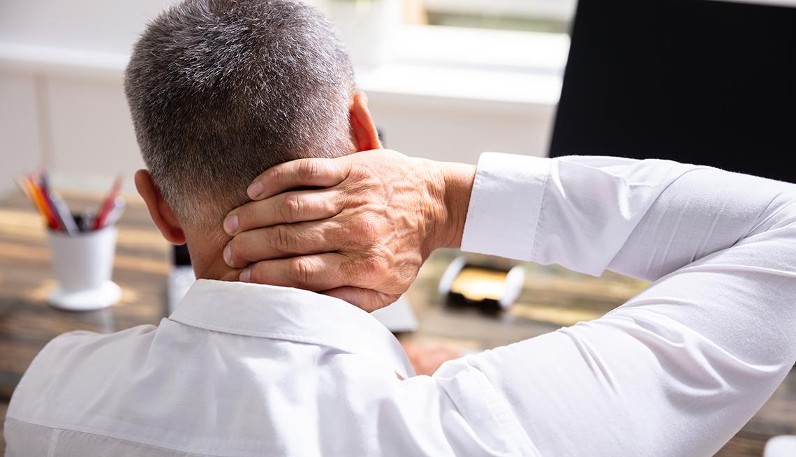 Hombre con la mano en el cuello dolorido frente a su computadora