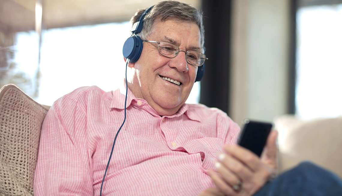 A man wearing earphones, listening to music relaxing on couch