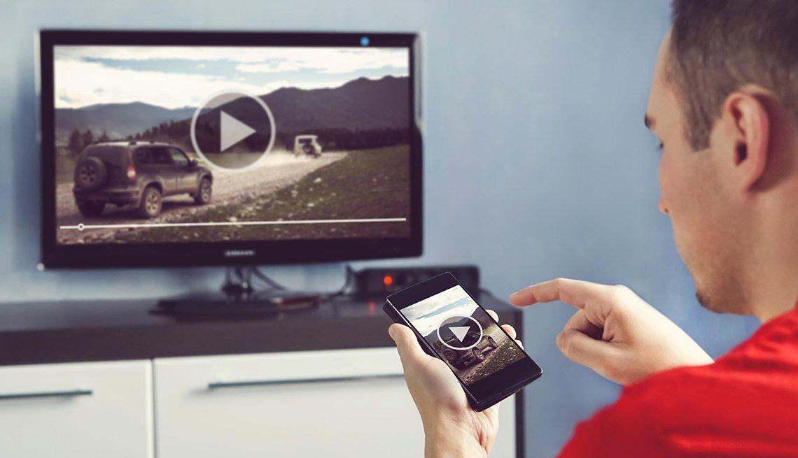 Hombre transfiere video del teléfono a la pantalla de TV