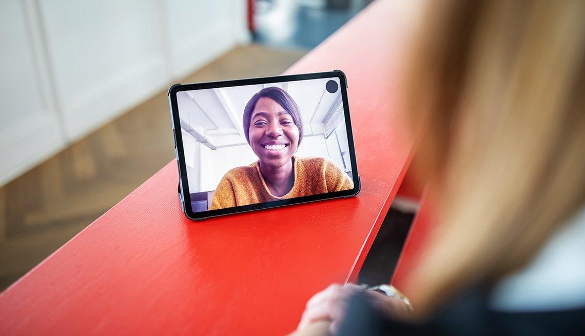 Mujer hablando con una colega en una videollamada