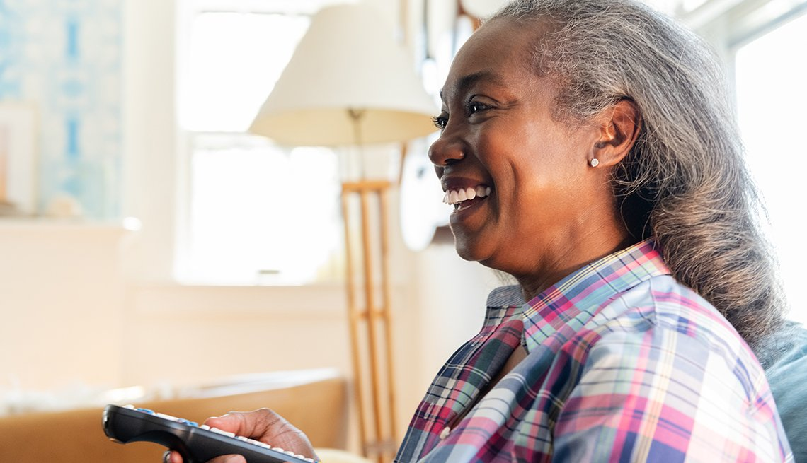 African American woman holding television remote
