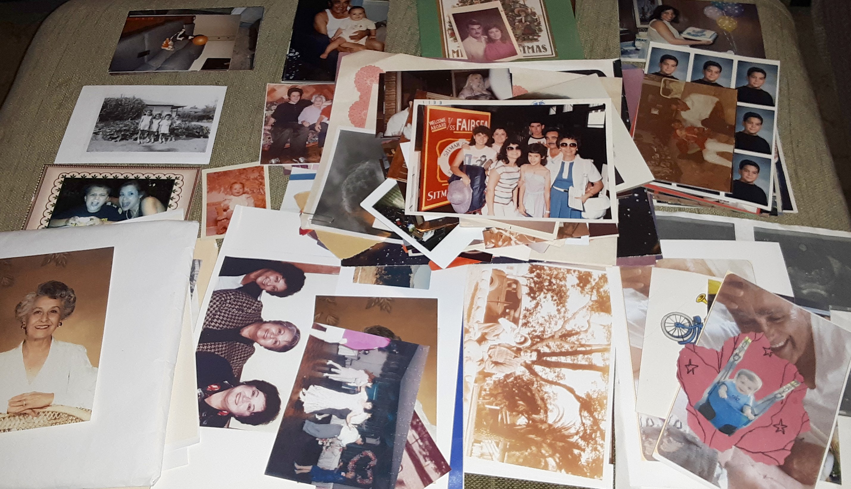 dozens of old family photos school photos and portraits are spread out on top of a bed