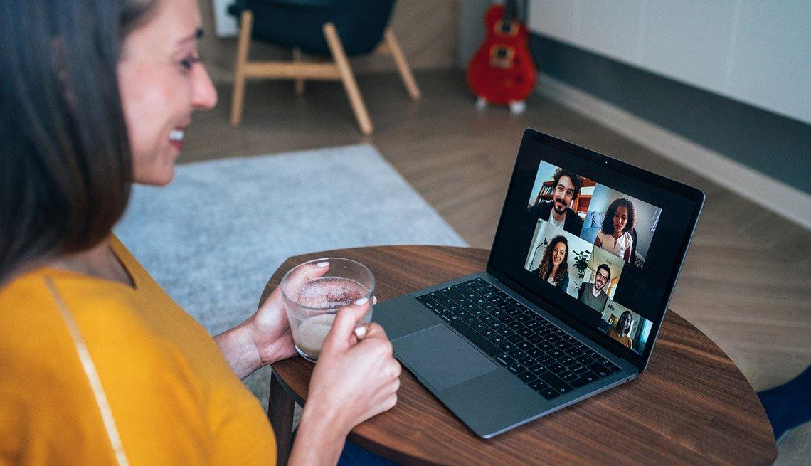 Mujer que usa una computadora portátil para una videoconferencia con varias personas