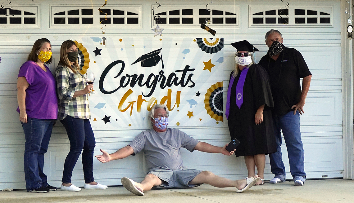 Linda White, third from right, poses with family and friends as she wears her cap and gown while celebrating graduating with a bachelor of science in elementary education and special education from Grand Canyon University during the coronavirus outbreak,