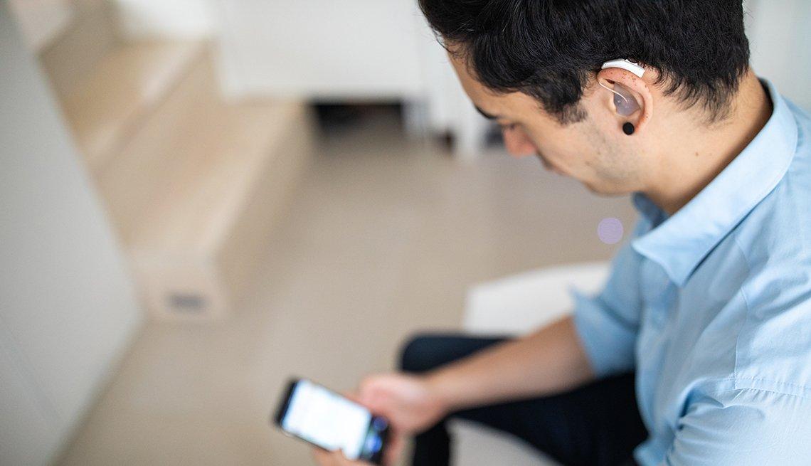 Un hombre con audífono en el oído mira su teléfono
